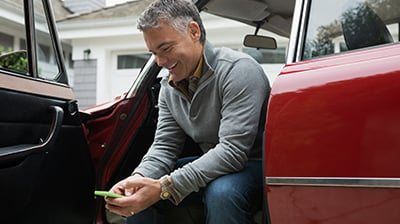 Man using mobile smartphone sitting in vehicle with door open