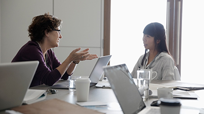 Two businesswomen in discussion during meeting.