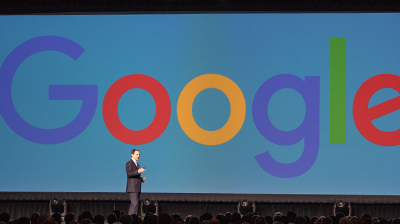 CEO Reid Standing in front of screen with Google logo being displayed.