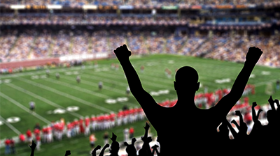 Silhouette of an excited sports fan at a football game